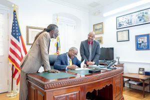 Senator Postive Nelson and Governor Albert Bryan sign medical marijuana bill.